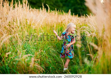 beautiful little girl laughs and rotates outdoors in a meadow during sunset - stock photo