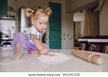 beautiful little girl learns to cook a meal in the kitchen - stock photo