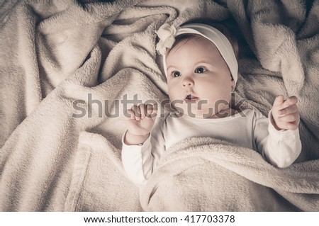 Beautiful little girl lies on her back and posing - stock photo