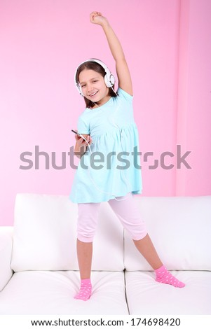 Beautiful little girl listening to music and dancing on sofa  and listening to music, on home interior background