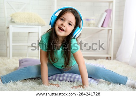 Beautiful little girl listening to music in room - stock photo