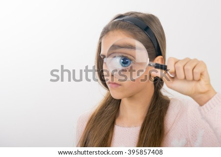 Beautiful little girl looking through a magnifying glass. Funny teen looking through a magnifying glass
