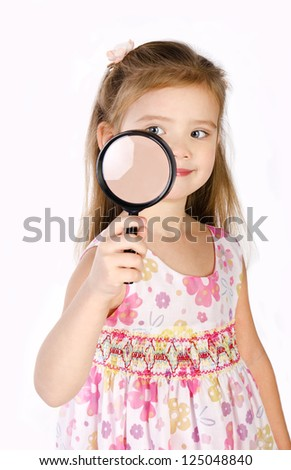 Beautiful little girl looking through a magnifying glass isolated on white - stock photo