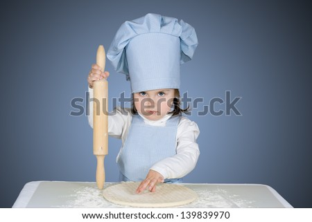 Beautiful little girl master chief cooking pizza - stock photo