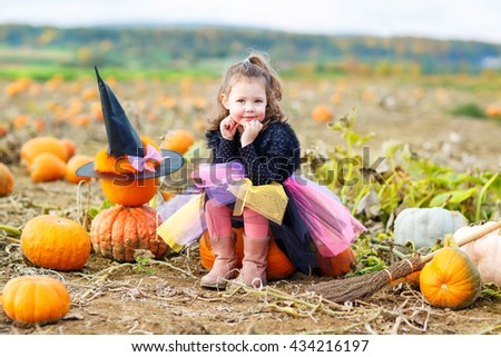 Beautiful little girl of 3 years wearing halloween witch costume having fun on a pumpkin farm. Traditional family festival with children.