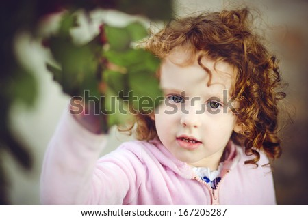 Beautiful little girl on a background of green leaves, look at the camera, close up.