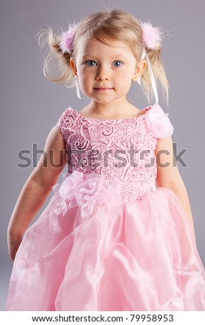 Beautiful little girl on a gray background