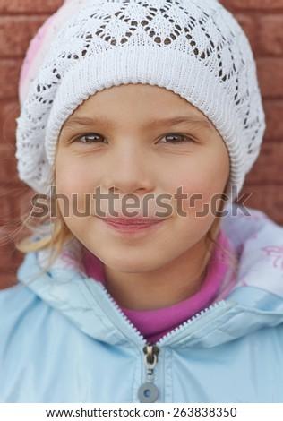 Beautiful little girl on haunches beside brick wall. - stock photo