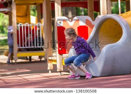 Beautiful little girl on outdoor playground at summertime - stock photo