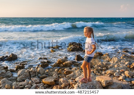 Beautiful little girl on the beach at sunset