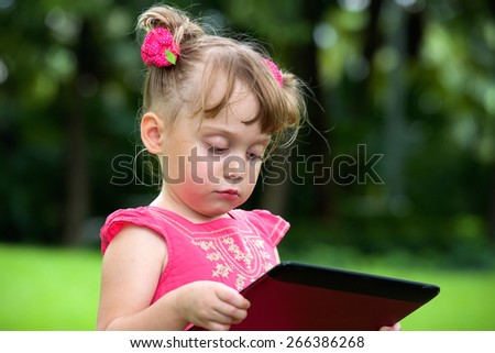Beautiful little girl outdoor with tablet pc on hands - stock photo