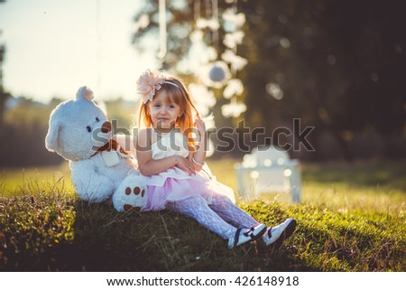 beautiful little girl outdoors with bear - stock photo