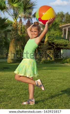 Beautiful little girl play with a ball outdoor