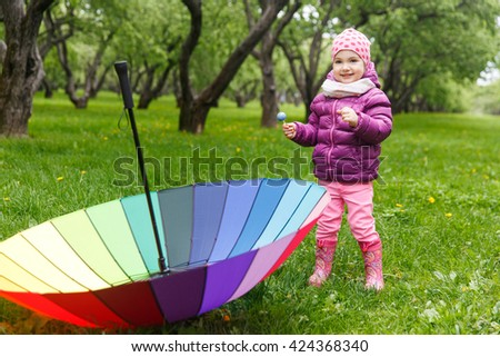 Beautiful little girl playing in green summer park with an umbrella rainbow colors