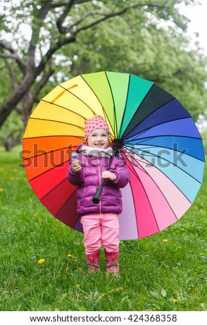 Beautiful little girl playing in green summer park with an umbrella rainbow colors - stock photo