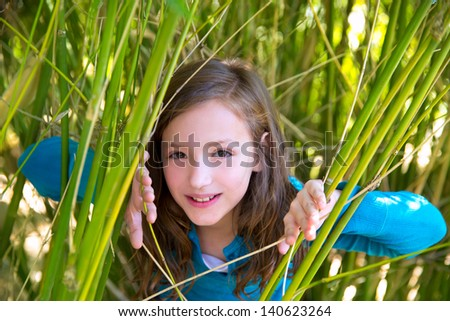 beautiful little girl playing in nature  peeping from green canes - stock photo