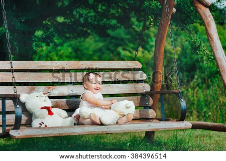 Beautiful little girl playing on a wooden bench toys in the garden, a nice summer day, children's party - stock photo