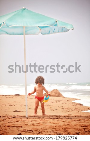 Beautiful little girl playing on the beach - stock photo