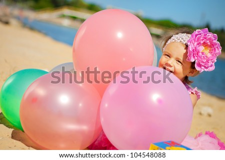 Beautiful little girl playing with air balloons at the beach