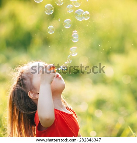 Beautiful little girl playing with soap bubbles nature, grass and dandelion. Portrait of a child in warm colors at sunset