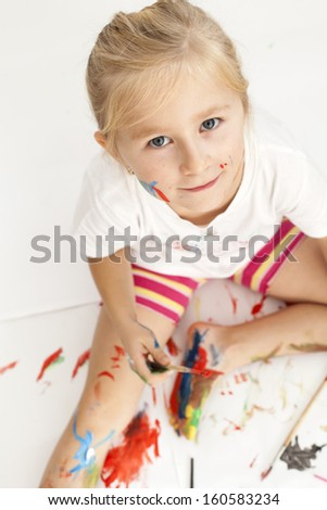 beautiful little girl playing with the paint - stock photo