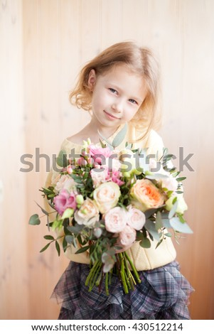 Beautiful little girl posing with a large bouquet of flowers - stock photo