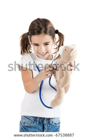 Beautiful little girl pretending to be a nurse and auscultate her teddy-bear - stock photo