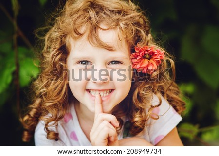Beautiful little girl putting finger up to lips and ask silence. Toning photo. - stock photo