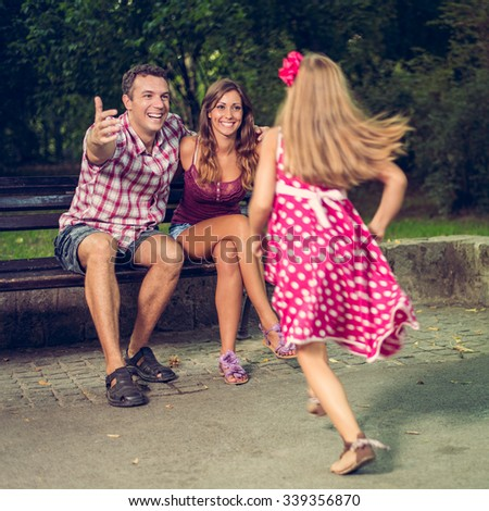 Beautiful little girl race to embrace her parents in the park.