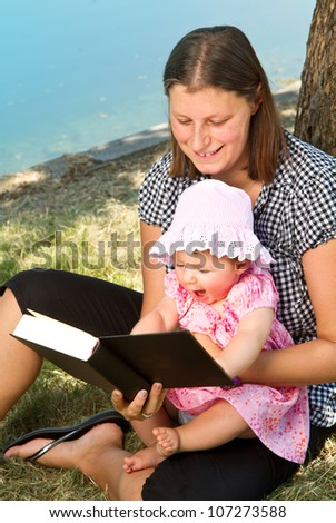 beautiful little girl reading book with her mother - stock photo