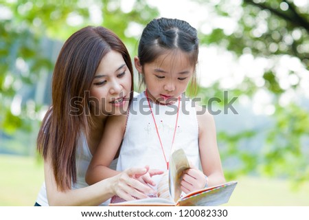 Beautiful little girl reading book with her mother and smiling. Summer park in background. - stock photo