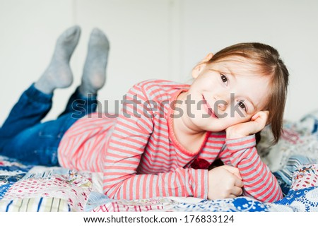Beautiful little girl resting on a bed