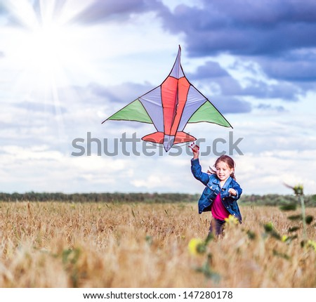 beautiful little girl run with a kite in a field of wheat