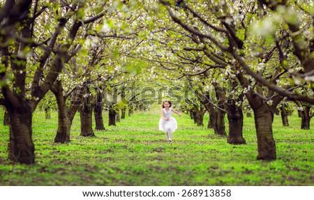 beautiful little girl running in the flowered garden - stock photo