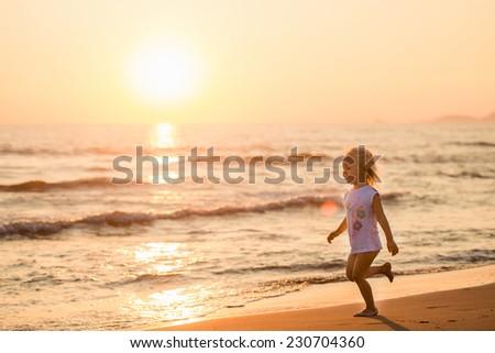 Beautiful little girl running on a beach at sunset, Italy, Forte dei Marmi - stock photo