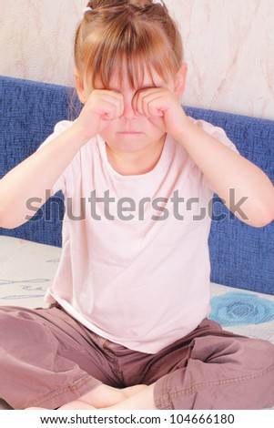 Beautiful little girl scratching her eyes - stock photo