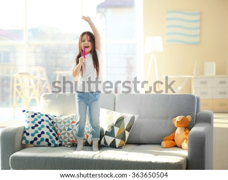 Beautiful little girl singing in a pink hairbrush and has fun in the room