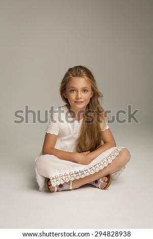 Beautiful little girl sitting - stock photo