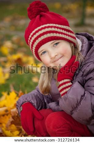 Beautiful little girl sitting among autumn leaves - stock photo