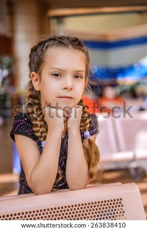 Beautiful little girl sitting at table and thinks. - stock photo