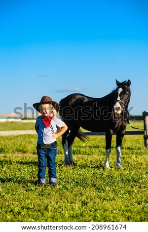beautiful little girl sitting on a cowboy background horse on a green meadow and blue sky. Nearby stand the a bucket of carrots and apples - stock photo