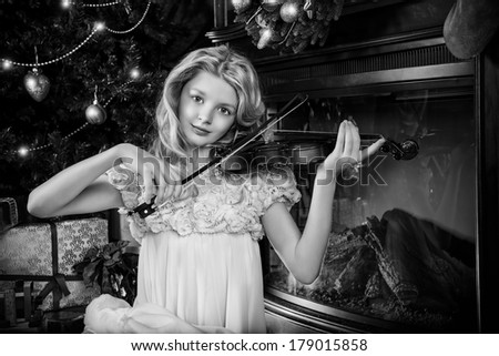 Beautiful little girl sitting on a floor near the fireplace and Christmas tree and playing the violin. - stock photo