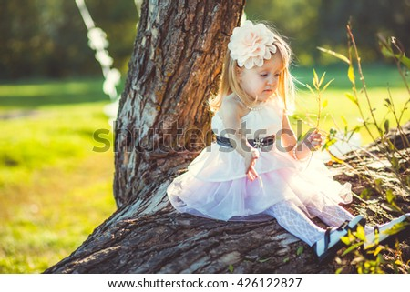 beautiful little girl sitting on a tree