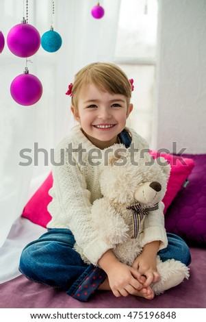 Beautiful little girl sitting on a windowsill and embraces a teddy bear. Window decorated with New Year's balls
