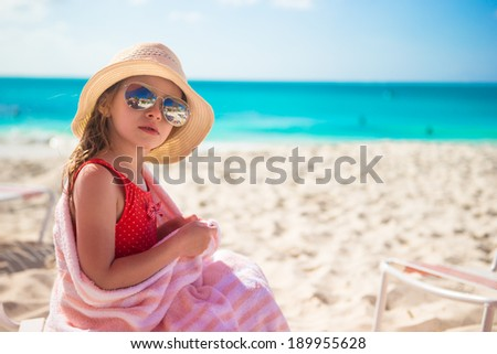 Beautiful little girl sitting on chair at beach during summer vacation - stock photo