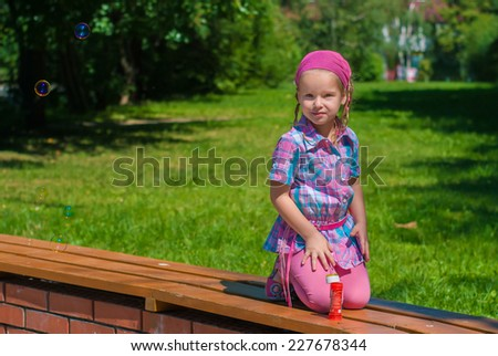 Beautiful little girl sitting on her knees on a bench in the park - stock photo