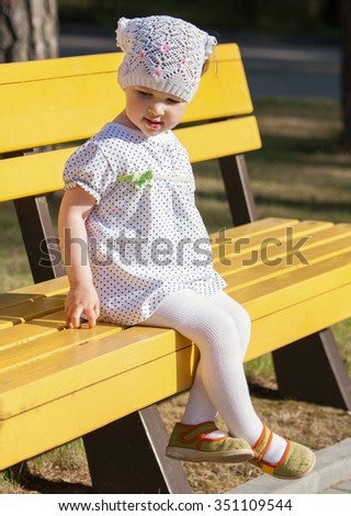 Beautiful little girl sitting on the bench in a park - stock photo