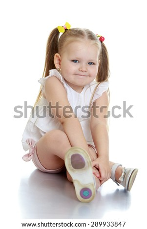 Beautiful little girl sitting on the floor - isolated on white background