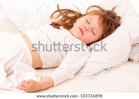 Beautiful little girl sleeping in bed - stock photo