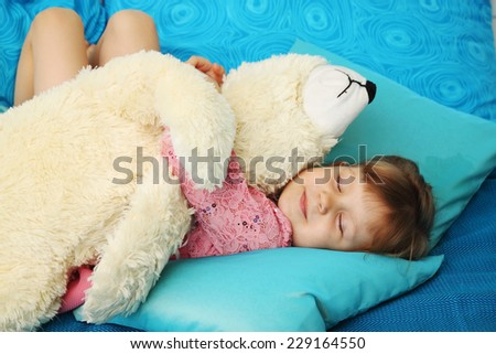 Beautiful little girl sleeping with teddy bear - stock photo